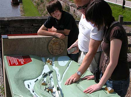 A small group touch the tactile map and compare it with the canal basin in the background.